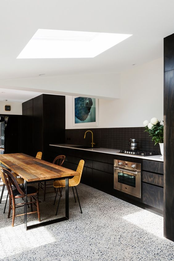 08-white-terrazzo-floor-contrasts-with-black-kitchen-cabinets-and-stained-wood-furniture